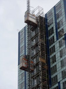 Image Project Hemel Showing Close Up View Of UBS Twin Mid Speed Construction Hoists And Common Tower System